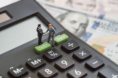 Financial tax cuts or reduce concept, miniature people businessmen handshaking standing on TAX minus button on calculator with ba royalty free stock images