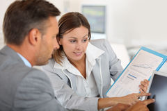 Financial team checking statistics on computer Stock Images