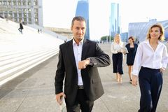 Financial team members passing with tablet, cases and looking at. Employees of financial organization walking in   with tablet and document cases in  . Concept Stock Images