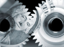 Financial teamwork. US dollar bank note overlaid onto cog wheels Stock Photo