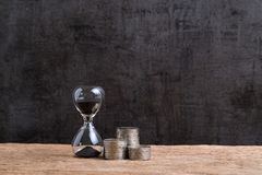 Financial time or long term investment concept with hourglass or. Sandglass and stack of coins on wooden table with textured black cement wall background and Stock Image