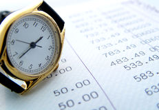 Financial times. Watch resting on financial sheets Stock Photos