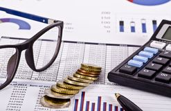 Financial tools, calculator, pen and specs over a report royalty free stock photography