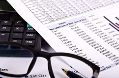Financial tools, calculator, pen and spectacles over a financial report royalty free stock photo