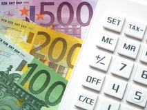 Financial transactions. Euro bills lying next to a calculator Royalty Free Stock Image