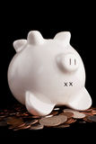 Financial trouble. A dead piggy bank signifies saving problems or recession biting problems. Isolated against white royalty free stock image