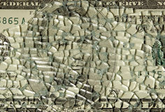 Financial troubles. Broken glass over a five dollars bill Stock Photo