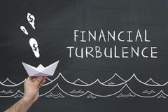 Financial turbulence concept on blackboard. Male hand with paper boat and text on chalkboard: financial turbulence Royalty Free Stock Photography