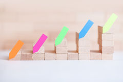 Business wood graph with stickers. Small business building with small wood cube Stock Image