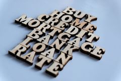 Financial words from wooden letters. House symbol or arrows. Selective focus. Shallow depth of field. Purchase, house, loan, bank