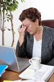 Financial Worries. Mature business woman at her desk, eyes closed, worried about bills and financial problems Royalty Free Stock Images