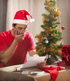 Financial Xmas Stress. Caucasian man looking at the disastrous Xmas budget and expenses Stock Image
