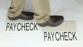 Financially Living. Person stepping from one paycheck to another paycheck to illustrate the phrase living paycheck to paycheck stock footage