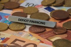 Financiamento de deficit - a palavra foi imprimida em uma barra de metal a barra de metal foi colocada em diversas cédulas Fotos de Stock