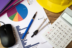 Financie el gráfico con la pluma, el casco de la construcción, la calculadora y el othe imagen de archivo