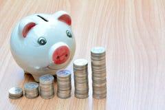 Financie moedas e mealheiro da pilha na tabela de madeira Foto de Stock Royalty Free