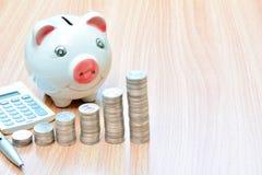 Financie moedas e mealheiro da pilha na tabela de madeira Imagem de Stock