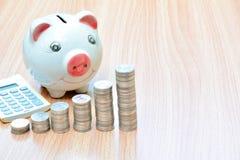 Financie moedas e mealheiro da pilha na tabela de madeira Fotos de Stock