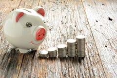 Financie moedas e mealheiro da pilha na tabela de madeira Imagens de Stock