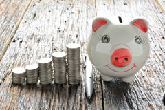 Financie moedas e mealheiro da pilha na tabela de madeira Fotografia de Stock