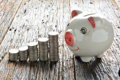 Financie moedas e mealheiro da pilha na tabela de madeira Foto de Stock