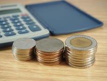 Financie o negócio, a pilha das moedas, o dinheiro e a calculadora no fundo de madeira fotos de stock royalty free