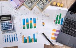 Financieel concept - bedrijfsgrafiek, euro, dollar en calculator op bureau stock foto's