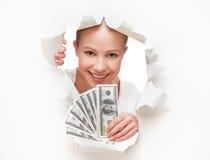Financieel concept, gelukkige vrouw met geld in handen die dollorov door een gat in een leeg Witboek gluren royalty-vrije stock foto