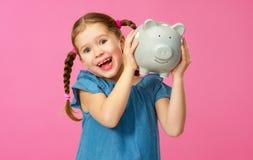 Financieel concept het kleingeld van kinderen kindmeisje met spaarvarken op een gekleurde roze achtergrond stock afbeelding