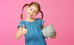 Financieel concept het kleingeld van kinderen kindmeisje met spaarvarken op een gekleurde roze achtergrond stock fotografie