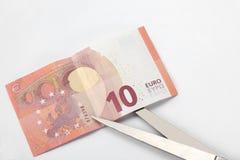 Financieel concept: snijd de schuld een euro rekening tien, een paar van schaar en een calculator op witte achtergrond met exempl stock foto