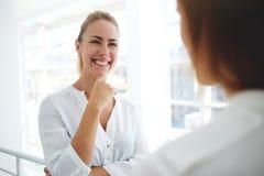financier de jeune femme avec le beau sourire écoutant son collègue tout en se tenant dans l'intérieur moderne de bureau Image libre de droits