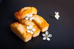 Financier français de gâteau d'amande de concept de nourriture mini sur le St noir d'ardoise Photographie stock