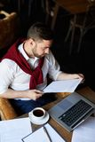 Financier with paper. Contemporary financier reading paper with statistic table while working in cafe royalty free stock image