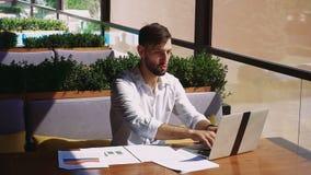 Financiero americano que trabaja con los documentos del ordenador portátil y del diagrama en la tabla almacen de video
