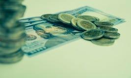 Financiero con la moneda y el billete de banco de la pila Imagenes de archivo