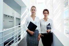 Financiers féminins réussis tenant le pavé tactile et les documents tout en se tenant dans l'intérieur moderne de bureau, Images stock