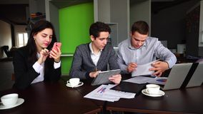 Financiers, two men and woman are loaded with work and use gadgets for work, sit at desk with documents in modern day stock footage