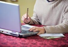 Financiert: Mens bij Laptop het Schrijven Controles voor Rekeningen royalty-vrije stock afbeelding