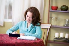 Financiert: Vrouw het Schrijven Controles aan Loonsrekeningen royalty-vrije stock afbeelding