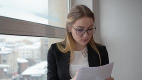 Financiervrouw die bedrijfsdocumenten kijken die zich terug naar venster in bureau bevinden stock footage