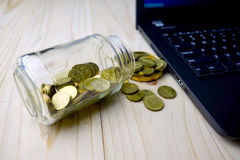 Financing concept. Golden coins with glass container and laptop Royalty Free Stock Photography