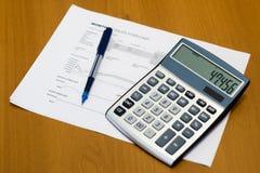 Finans, bankrörelsen och affärsidé med diagram, grafer, räknemaskinen och pennan på träbakgrund Arkivfoto