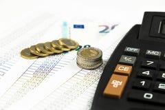 Finans, euromynt, penna och miniräknare på vit bakgrund Arkivfoton
