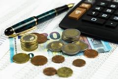 Finans, euromynt, penna och miniräknare på vit bakgrund Arkivbild