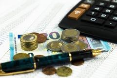 Finans, euromynt, penna och miniräknare på vit bakgrund Arkivbilder