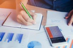 Finans och besparing för asiatisk hand beräknande med mobiltelefonen på wood tabellbakgrund royaltyfri foto