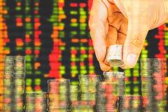 Finanse i oszczędzania pieniądze bankowości pojęcie, nadzieja inwestora pojęcie, Męska ręki kładzenia pieniądze moneta jak sterta Obraz Stock
