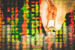 Finanse i oszczędzania pieniądze bankowości pojęcie, nadzieja inwestora pojęcie, Męska ręki kładzenia pieniądze moneta jak sterta Zdjęcia Stock