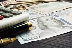 Finanser eller lånbegrepp Dollarsedlar och räknemaskin på ett skrivbord royaltyfri foto